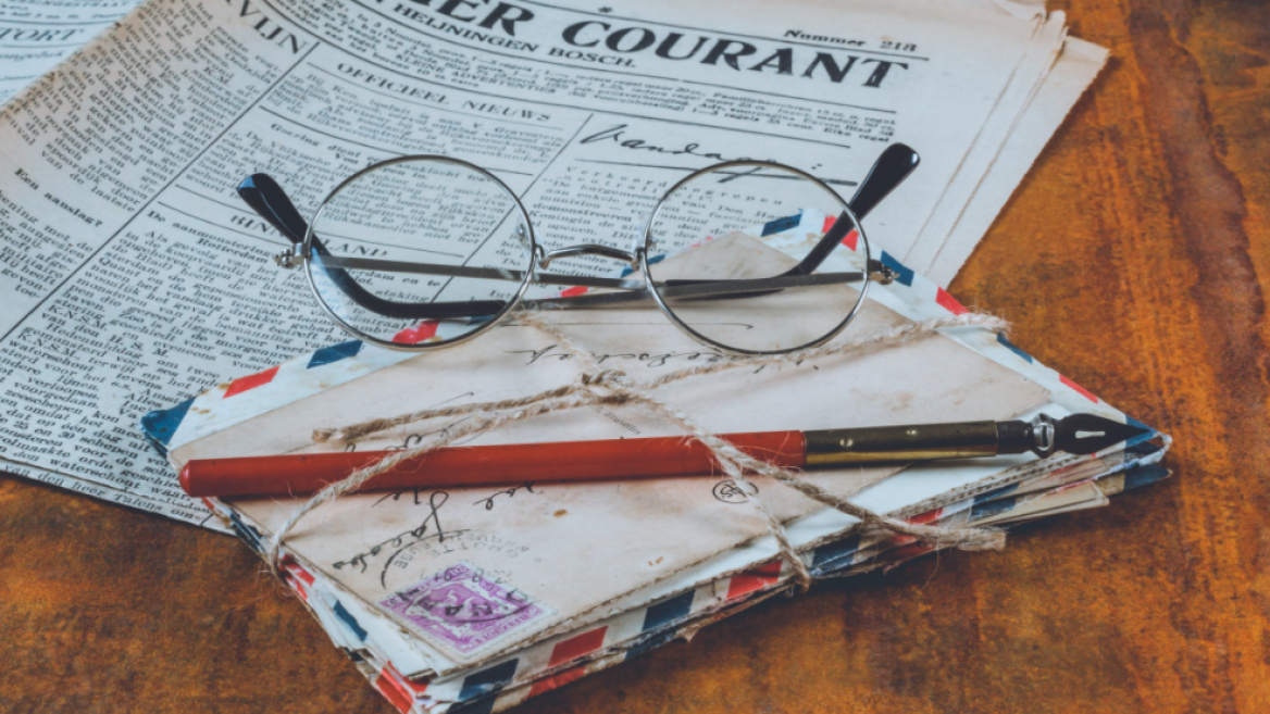 round-framed glasses sitting on a pile of old letters with a newspaper in the background